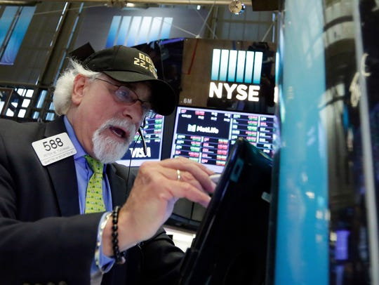 "Trader Peter Tuchman wears a ""Dow 22,000"" hat as he"