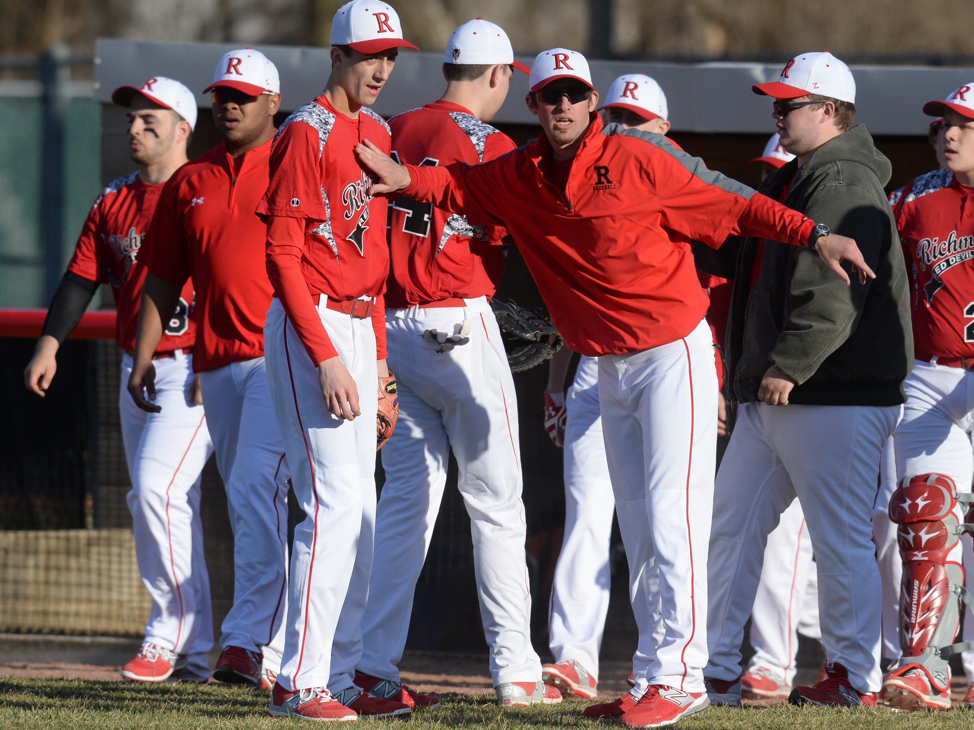 Richmond baseball coach Tyler Lairson greets players as they return to the dugout during a baseball game Tuesday, March 31, 2015, on John Cate Field at McBride Stadium.