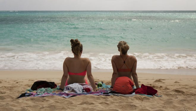 In this May 19, 2015 photo, Ali Junell, of Portland, Ore., left, and Kristen Carmichael, of Los Angeles, sit on the beach at Waimanalo Bay Beach Park in Waimanalo, Hawaii. The beach was listed as No. 1 on the 2015 list of best beaches, a list compiled annually by Florida International University Professor Stephen Leatherman, also known as Dr. Beach.