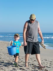 A father and his son walk along Juno Beach as they participate in Loggerhead Marinelife Center's monthly beach cleanup on Jan. 21.