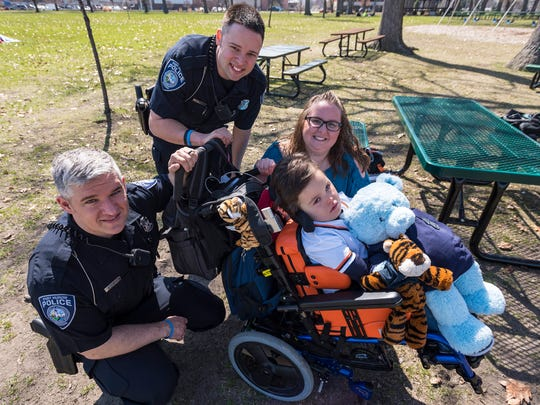 Ben Welser, 3, pictured Monday, April 30 with his adopted mother Jamie Welser, right, and Port Huron Police officers Brandon Rossow, left, and Derek Paret. The officers found Ben, who suffers from a brain malformation, wrapped in a blanket on a porch when he was two months old.