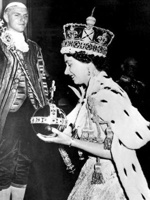 Britain's Queen Elizabeth II wearing the bejeweled Imperial Crown and carrying the Orb and Scepter with Cross, leaves Westminster Abbey, London, at the end of her coronation ceremony June 2, 1953.
