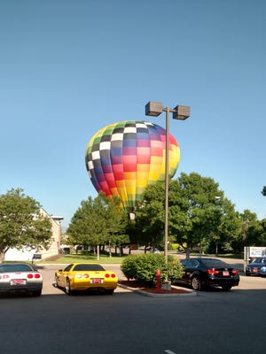 A hot air balloon lands between Natural Grocers and Troutman Parkway on Thursday, June 8, 2017.