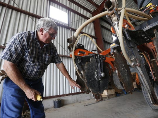 Bob Bowman shows some of the details on the strip till machine he built and modified to spray both anhydrous ammonia and a nitrogen fertilizer onto his crops Friday, Aug. 7, 2015, on his farm near DeWitt, Iowa.
