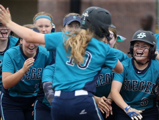 Siegel's Caitlyn McCrary celebrates her solo home run with her teammates during a District 7-AAA softball championship. Siegel defeated Stewarts Creek 5-0.