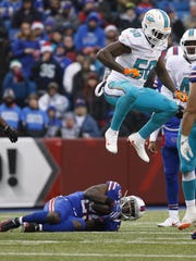 Miami Dolphins defensive end Andre Branch (50) jumps to avoid Buffalo Bills running back LeSean McCoy (25) during the second half of an NFL football game Saturday, Dec. 24, 2016, in Orchard Park, N.Y. (AP Photo/Bill Wippert)