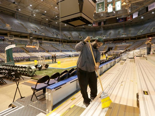 Jeffrey Greer of Performance Clean cleans the bleachers at the BMO Harris Bradley Center.