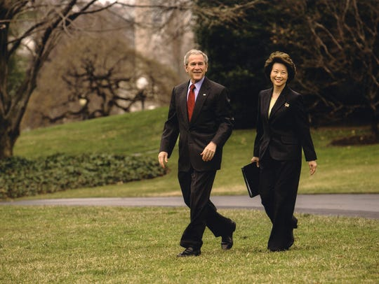 Chao, then the Labor secretary, walks with then-president