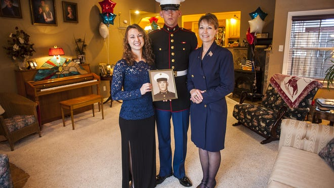 LynDee Feisthamel, left, holds her father's portrait and stands with her brother, Nic, and her mother, LeAnn. LynDee has maintained a 4.0 GPA while participating in golf, basketball, track and cross country teams at Great Falls High School. Nic recently returned from boot camp at the Marine Corps Recruit Depot in San Diego, the same place their father attended approximately 50 years ago.