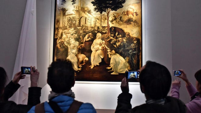 "In this Monday, March 27, 2017 file photo, visitors take pictures of Leonardo da Vinci's ""Adoration of the Three Wise Men"", returned to the public of the Uffizi museum after 6 years of study and restoration, in Florence, Italy."