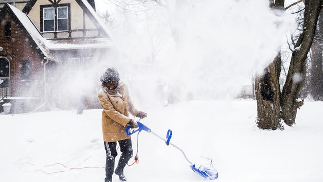 Wind pushes snow back onto Sarah Allen as she clears her driveway and sidewalks with a snowblower during a winter snowstorm Monday, Jan. 28, 2019, in Flint. Mich.