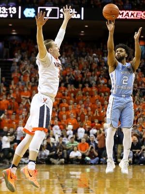 North Carolina guard Joel Berry II, right, shoots the ball as Virginia guard Kyle Guy defends during the first half at John Paul Jones Arena in Charlottesville, Va.