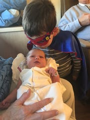 Cooper McDevitt, 3, goes to give his sister, Kathryn,