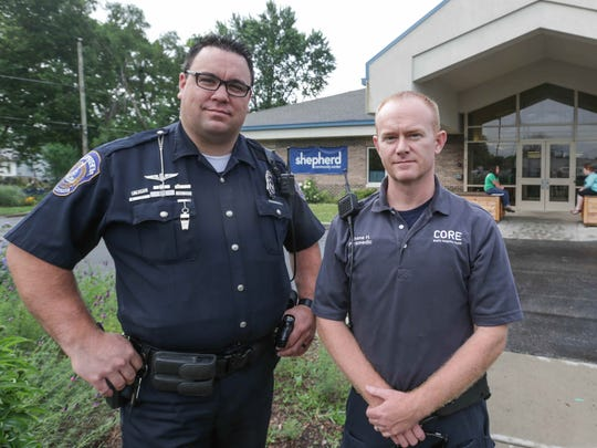IMPD patrolman Adam Perkins, left, and CORE paramedic Shane Hardwick, right, work together as part of the Shalom Project, a community policing/health effort led by the Shepherd Community Center, Wednesday June 15, 2016.