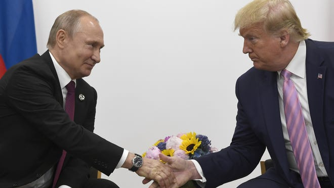 In this June 28, 2019, file photo President Donald Trump shakes hands with Russian President Vladimir Putin during a bilateral meeting on the sidelines of the G-20 summit in Osaka, Japan.