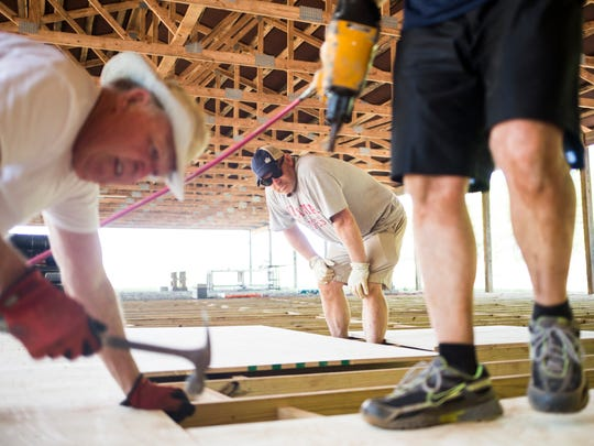 Duane Jenkins, left, Ray Turner, center, and Matthew Gillum work on the new Blue Jar Barn on Thursday in Anderson.
