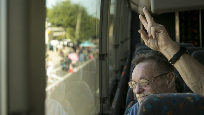 Oden Gordon, 63, a Vietnam War veteran, waves from inside a Tour West America charter bus to people who gathered along the Phoenix Veterans Day Parade route on Nov. 11, 2016.