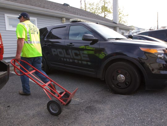 A department of public works worker pulls a hand truck