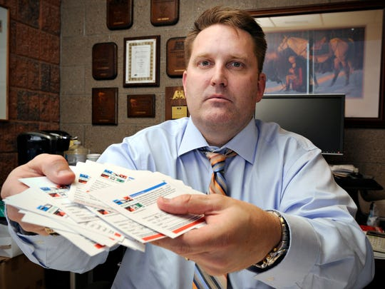 Sen. John Pederson holds a stack of cards Friday he