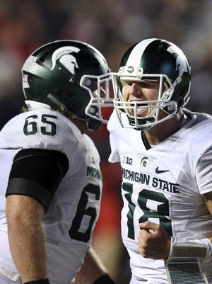 Michigan State quarterback Connor Cook, right, celebrates with offensive lineman Brian Allen late in the second half of the 31-24 victory over Rutgers on Saturday night.