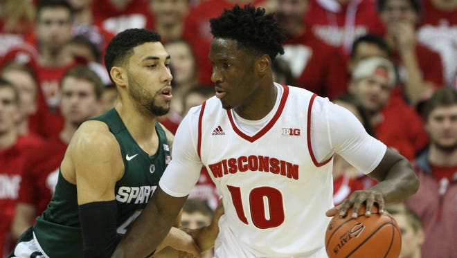 Jan 17, 2016; Madison, WI, USA; Wisconsin Badgers forward Nigel Hayes (10) moves the ball against Michigan State Spartans guard Denzel Valentine (left) during the first half at the Kohl Center.