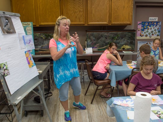 Kim McGrew-Liggett explains how the water and paint works together at advanced art camp at John James Audubon Park Wednesday morning.