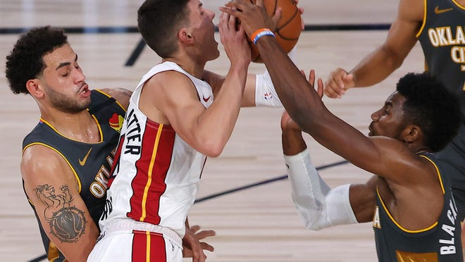 Oklahoma City Thunder's Hamidou Diallo, right, and Abdel Nader defend against Miami Heat's Tyler Herro during the first quarter of an NBA basketball game Wednesday, Aug. 12, 2020, in Lake Buena Vista, Fla.