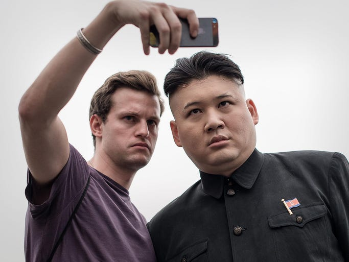 Howard, who goes by his first name to keep his career as a singer and impersonator separate, is dressed as North Korean leader Kim Jong Un as he poses with a tourist on Nov. 27 in Hong Kong. Howard considers himself to be the world's first professional Kim Jong Un impersonator.