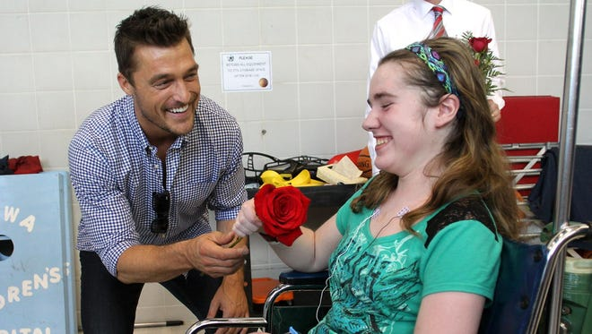 Chris Soules, former Bachelor and Dancing with the Stars contestant, offers a rose to 13-year-old Makenzie Cox of New Hampton at the Ladies Football Academy kickoff event to benefit the University of Iowa Children's Hospital on Friday.