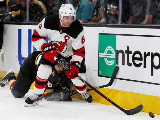 New Jersey Devils defenseman Andy Greene, top, works
