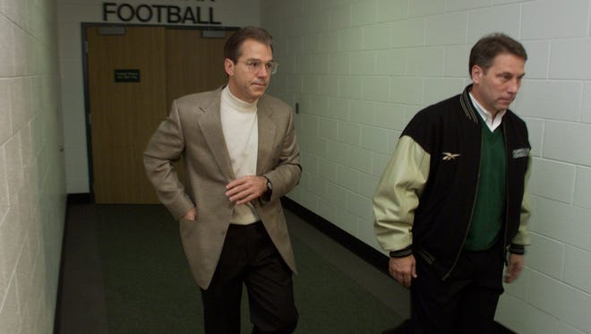Former Spartans football coach Nick Saban, left, accompanied by Spartans basketball coach Tom Izzo, leaves a morning team meeting Tuesday, Nov. 30, 1999, at the Duffy Daugherty football building on the East Lansing campus, where he told his team that he will leave MSU to take over LSU.