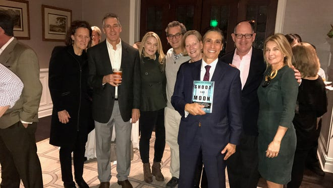 "Dr. Carl Giordano, front, holding his book ""Shoot the Moon"" at a book release event at the Morris County Golf Club.  Pictured with him are friends and family including Darcy and Peter Caldwell, Jenn and Darren Burns, Virginia and Mike Ranger and his wife, Abbie Giordano."