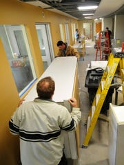 Workers moves cabinets  into place Monday, Dec. 7,
