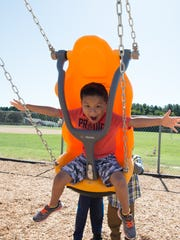 Randy Lopez, a first-grader at Georgetown Elementary School, swings on a therapeutic swing with safety harness at the district's new fully accessible playground.
