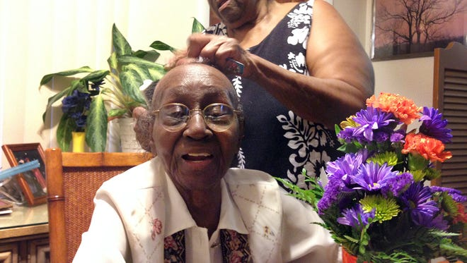Regina Smith's daughter, Snoozie, fixes her hair on Smith's 100th birthday.