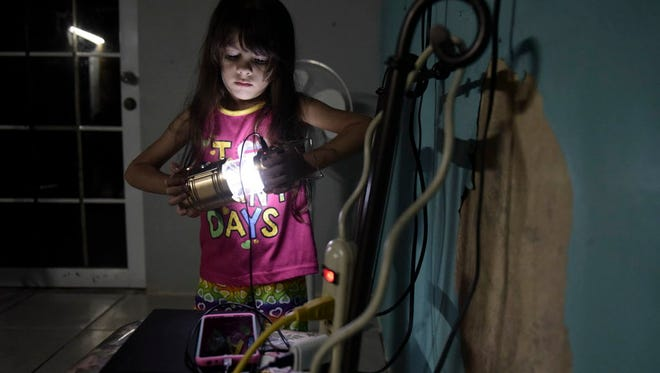 Melanie Oliveras Gonzalez, 6, holds a lantern in the living room of her house Dec. 21 in Morovis, Puerto Rico. All electronics are connected at night to an inverter plugged to the family car's battery.