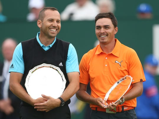 Runners up Sergio Garcia of Spain, left, and Rickie Fowler of the US smile with their trophies after Rory McIlroy of Northern Ireland won the British Open Golf championship at the Royal Liverpool golf club, Hoylake, England, Sunday July 20, 2014. (AP Photo/Peter Morrison)