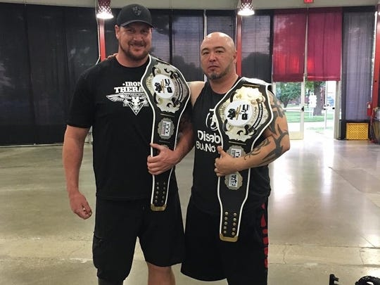 National Adaptive Strongman champion Chad Macklin, left,  stands with seated strongman champion Tommy Ahn in Columbus, Ohio in May.