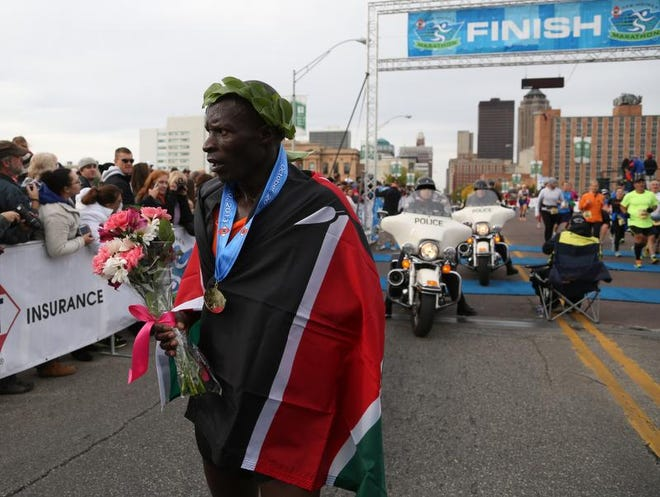 David Tuwei, wrapped in the flag of his native country of Kenya, finished first in the Des Moines Marathon Sunday.