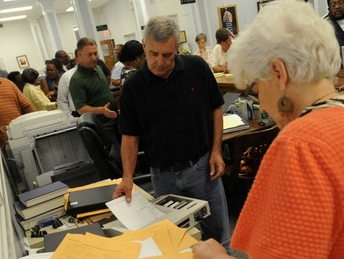 City Election Commission Chairman George Decoux, center, runs ballots through the scanner.