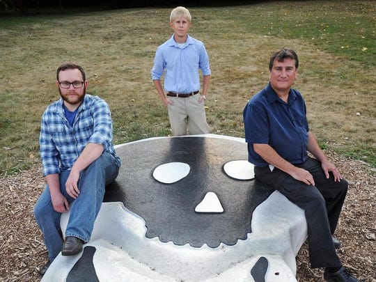 "Indiana Media Production Alliance executives, from left, Benjamin Dewhurst, Glenn Pratt and Chuck Budreau pose on the head of the original ""Funky Bones"" sculpture in Indianapolis."
