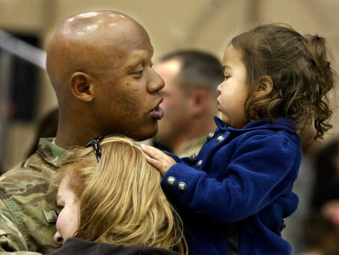 Sgt. Juan Marte was greeted by his wife Heather and daughter Aerith, 2. Marte was one of 240 soldiers from the 4th Brigade Combat Team to return Monday to Fort Campbell.
