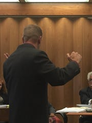 Suspended Indianapolis Metropolitan Police Department officer Johnathan Burger demonstrates the move he used to subdue his wife. He testified before the Civilian Police Merit Board on Tuesday, Nov. 10, 2015.