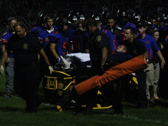 Kyle Becker's teammates crossed the field to wish him well as he is carted to a waiting ambulance.