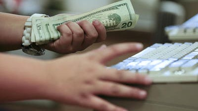 In this Friday, Nov. 23, 2012 file photo, a cashier rings up a cash sale at a Sears store, in Las Vegas. The Commerce Department says consumer spending fell 0.1 percent in April, reflecting reductions in purchases of durable goods such as autos and in services such as heating bills.