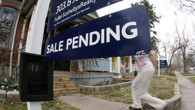 In this Saturday, March 17, 2012, photo, an unidentified woman passes by a pending sale sign outside home on the market in south Denver. The number of Americans who signed contracts to buy homes shot up in May. But the pace of buying this year remains slower than in 2013, in part because of sluggish sales during winter.