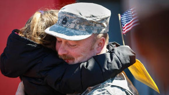 Sgt. 1st Class Daniel Dolinger of Newark gets a big hug from his granddaughter Kyleigh Patterson, 3, at Alumni Stadium on the DSU campus during the departure ceremony for the 198th Signal Battalion on Apr. 6, 2013.