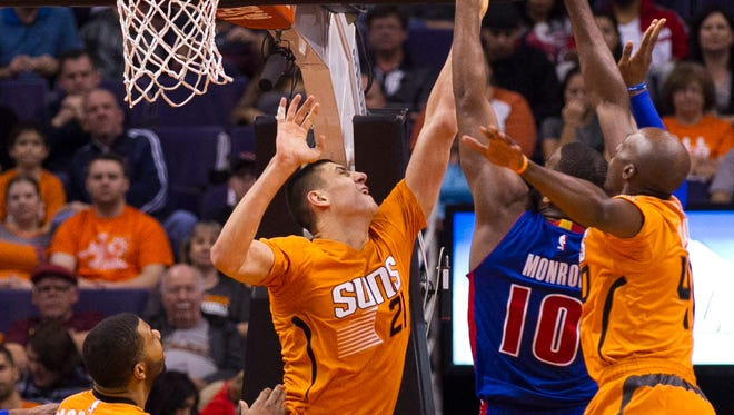 Suns center Alex Len blocks a shot from the Pistons' Greg Monroe during a game at US Airways Center in Phoenix on Dec. 12, 2014.