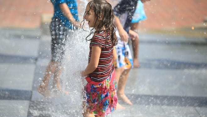 Yonah Amedi; age 5, plays in the Splasheville fountain at Pack Square Park during Organicfest in 2014.
