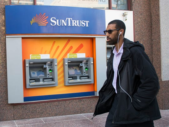 A man walks past a SunTrust bank ATM Oct. 11, 2016